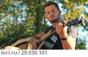 Купить «Man play guitar at forest», видеоролик № 29030101, снято 30 августа 2018 г. (c) Илья Шаматура / Фотобанк Лори