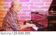Купить «Man musician playing the piano. He's wearing a plaid shirt, glasses, a gold watch, rings. Gray hair.», видеоролик № 29030305, снято 31 мая 2020 г. (c) Константин Шишкин / Фотобанк Лори