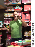 Купить «Adult man in front of difficult choice in store», фото № 29035841, снято 29 августа 2016 г. (c) Яков Филимонов / Фотобанк Лори