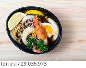 Купить «Image of spicy pan-Asian soup with squid, shrimp, egg noodles and sesame», фото № 29035973, снято 21 октября 2018 г. (c) Яков Филимонов / Фотобанк Лори