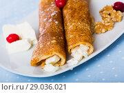 Купить «Dish of pancakes palachinki with filling from brynza and walnuts», фото № 29036021, снято 15 декабря 2018 г. (c) Яков Филимонов / Фотобанк Лори