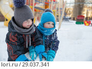 Купить «Two cute children boys in warm clothes in winter play in playground», фото № 29037341, снято 21 марта 2018 г. (c) Юлия Бабкина / Фотобанк Лори