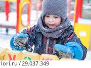 Купить «Мальчик 4 года зимой на детской площадке играет кубиками с буквами», фото № 29037349, снято 21 марта 2018 г. (c) Юлия Бабкина / Фотобанк Лори