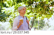 Купить «senior woman drinking coffee at park», видеоролик № 29037945, снято 21 августа 2018 г. (c) Syda Productions / Фотобанк Лори