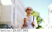 Купить «senior woman walks along city and drinks coffee», видеоролик № 29037993, снято 21 августа 2018 г. (c) Syda Productions / Фотобанк Лори