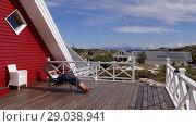 Купить «A woman reading a book lying in a trestle on a wooden terrace with a view of rocks, Averoy, Norway», видеоролик № 29038941, снято 1 сентября 2018 г. (c) Некрасов Андрей / Фотобанк Лори