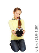 Купить «Маленькая девочка смотрит на будильник в руках и удивляется», фото № 29041301, снято 7 декабря 2013 г. (c) Александр Гаценко / Фотобанк Лори