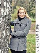 Купить «Девушка в осеннем пальто около дерева», фото № 29041309, снято 5 октября 2013 г. (c) Александр Гаценко / Фотобанк Лори