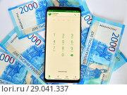 Phone with mobile application Sberbank online and money (2018 год). Редакционное фото, фотограф Володина Ольга / Фотобанк Лори