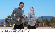 Купить «couple with earphones running over venice beach», фото № 29042713, снято 17 октября 2015 г. (c) Syda Productions / Фотобанк Лори