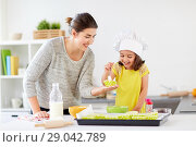 Купить «happy mother and daughter baking cupcakes at home», фото № 29042789, снято 20 октября 2017 г. (c) Syda Productions / Фотобанк Лори