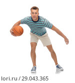 smiling young man dribbling basketball. Стоковое фото, фотограф Syda Productions / Фотобанк Лори