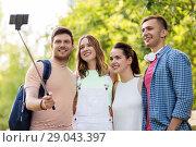 Купить «friends take picture by smartphone on selfie stick», фото № 29043397, снято 7 июля 2018 г. (c) Syda Productions / Фотобанк Лори