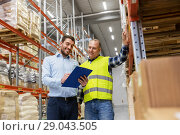Купить «worker and businessman with clipboard at warehouse», фото № 29043505, снято 9 декабря 2015 г. (c) Syda Productions / Фотобанк Лори