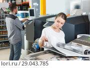 Купить «Young woman looking samples of wallpaper», фото № 29043785, снято 17 мая 2018 г. (c) Яков Филимонов / Фотобанк Лори