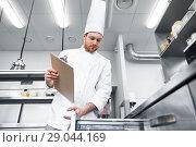 Купить «chef with clipboard doing inventory at kitchen», фото № 29044169, снято 2 апреля 2017 г. (c) Syda Productions / Фотобанк Лори