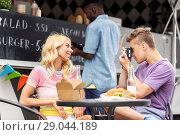 Купить «couple photographing by camera at food truck», фото № 29044189, снято 1 августа 2017 г. (c) Syda Productions / Фотобанк Лори