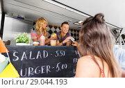 Купить «happy customers buying burger at food truck», фото № 29044193, снято 1 августа 2017 г. (c) Syda Productions / Фотобанк Лори