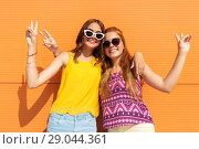 Купить «smiling teenage girls showing peace in summer», фото № 29044361, снято 19 июля 2018 г. (c) Syda Productions / Фотобанк Лори