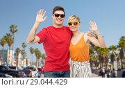 Купить «couple in sunglasses hugging and waving hands», фото № 29044429, снято 30 июня 2018 г. (c) Syda Productions / Фотобанк Лори