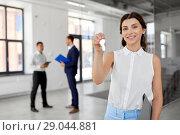 Купить «smiling realtor with keys and folder at new office», фото № 29044881, снято 8 июня 2018 г. (c) Syda Productions / Фотобанк Лори