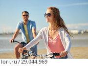 Купить «happy young couple riding bicycles at seaside», фото № 29044969, снято 23 июля 2017 г. (c) Syda Productions / Фотобанк Лори