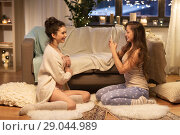 Купить «female friends photographing by smartphone at home», фото № 29044989, снято 21 января 2018 г. (c) Syda Productions / Фотобанк Лори