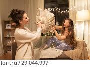 Купить «happy female friends having pillow fight at home», фото № 29044997, снято 21 января 2018 г. (c) Syda Productions / Фотобанк Лори