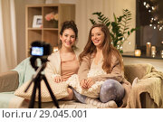 Купить «female bloggers with camera recording home video», фото № 29045001, снято 21 января 2018 г. (c) Syda Productions / Фотобанк Лори
