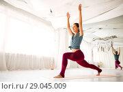 Купить «woman making high lunge exercise at yoga studio», фото № 29045009, снято 21 июня 2018 г. (c) Syda Productions / Фотобанк Лори