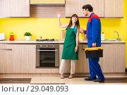 Купить «Woman with contractor at kitchen discussing repair», фото № 29049093, снято 20 июня 2018 г. (c) Elnur / Фотобанк Лори