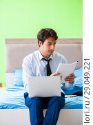 Купить «Businessman working in the hotel room», фото № 29049221, снято 21 июня 2018 г. (c) Elnur / Фотобанк Лори