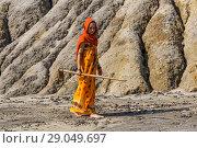 Купить «Young woman in a sari and hijab with a hoe in her hands in an arid, lifeless desert area», фото № 29049697, снято 2 сентября 2018 г. (c) Евгений Харитонов / Фотобанк Лори