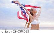 Купить «happy young woman with american flag on beach», видеоролик № 29050085, снято 24 августа 2018 г. (c) Syda Productions / Фотобанк Лори