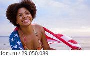 Купить «happy african woman with american flag on beach», видеоролик № 29050089, снято 24 августа 2018 г. (c) Syda Productions / Фотобанк Лори