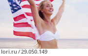 Купить «happy young woman with american flag on beach», видеоролик № 29050149, снято 24 августа 2018 г. (c) Syda Productions / Фотобанк Лори