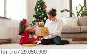Купить «mother and daughter with christmas gift at home», видеоролик № 29050909, снято 31 августа 2018 г. (c) Syda Productions / Фотобанк Лори