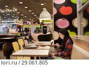 Купить «Девушка с мобильным телефоном в кафе», фото № 29061805, снято 26 августа 2018 г. (c) Victoria Demidova / Фотобанк Лори