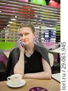 Купить «Девушка с мобильным телефоном в кафе», фото № 29061945, снято 26 августа 2018 г. (c) Victoria Demidova / Фотобанк Лори
