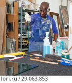 Купить «Positive craftsman inspecting finished product», фото № 29063853, снято 16 мая 2018 г. (c) Яков Филимонов / Фотобанк Лори