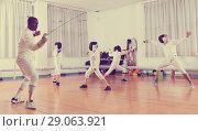 Купить «Coaches demonstrating to young athletes attack movements with rapier during fencing workout», фото № 29063921, снято 30 мая 2018 г. (c) Яков Филимонов / Фотобанк Лори