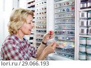 Купить «Female next to shelf with buttons», фото № 29066193, снято 23 мая 2019 г. (c) Яков Филимонов / Фотобанк Лори