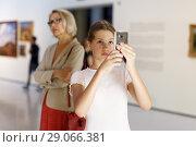 Купить «Teenage girl using phone in museum», фото № 29066381, снято 18 августа 2018 г. (c) Яков Филимонов / Фотобанк Лори