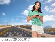 Купить «teenage girl in phones with smartphone on route 66», фото № 29066817, снято 30 июня 2018 г. (c) Syda Productions / Фотобанк Лори