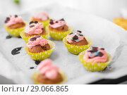 Купить «close up of frosted cupcakes or muffins on tray», фото № 29066865, снято 20 октября 2017 г. (c) Syda Productions / Фотобанк Лори