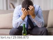 Купить «male alcoholic with bottle of beer at home», фото № 29066873, снято 24 ноября 2017 г. (c) Syda Productions / Фотобанк Лори