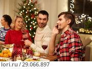 Купить «man calling on smartphone at christmas dinner», фото № 29066897, снято 17 декабря 2017 г. (c) Syda Productions / Фотобанк Лори