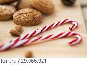 Купить «candy canes, cookies and almonds on board», фото № 29066921, снято 15 ноября 2017 г. (c) Syda Productions / Фотобанк Лори