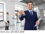 Купить «smiling realtor with keys and folder at new office», фото № 29067009, снято 8 июня 2018 г. (c) Syda Productions / Фотобанк Лори