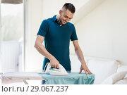 Купить «man ironing shirt by iron at home», фото № 29067237, снято 10 мая 2018 г. (c) Syda Productions / Фотобанк Лори